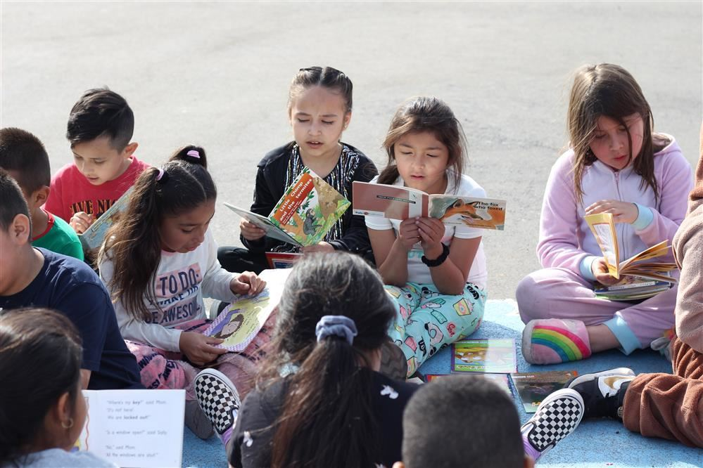 children reading on the blacktop